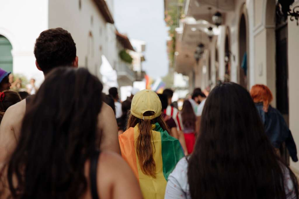 A woman wearing a yellow hat wearing a rainbow pride flag in the middle of a crowd during the lgbtq+